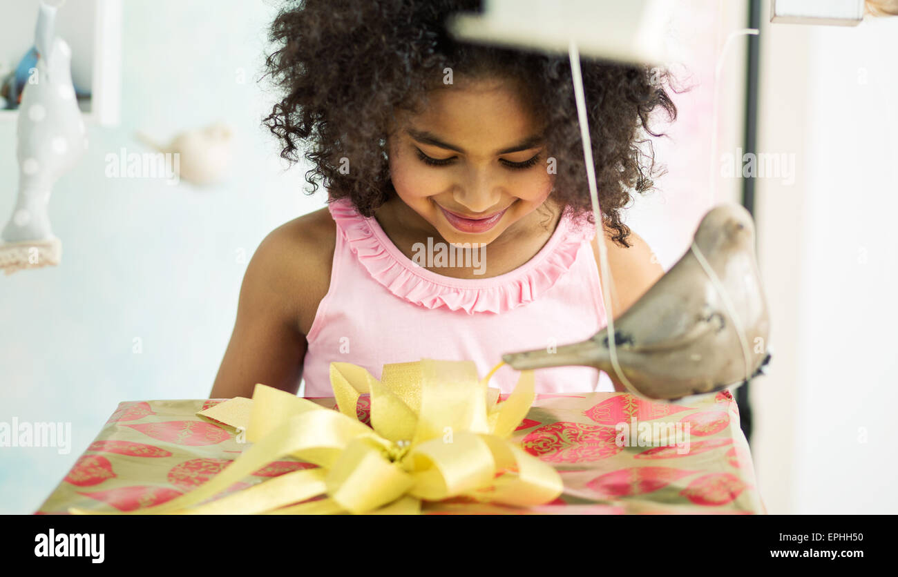 Adorable young girl opening the birthday gift - Stock Image