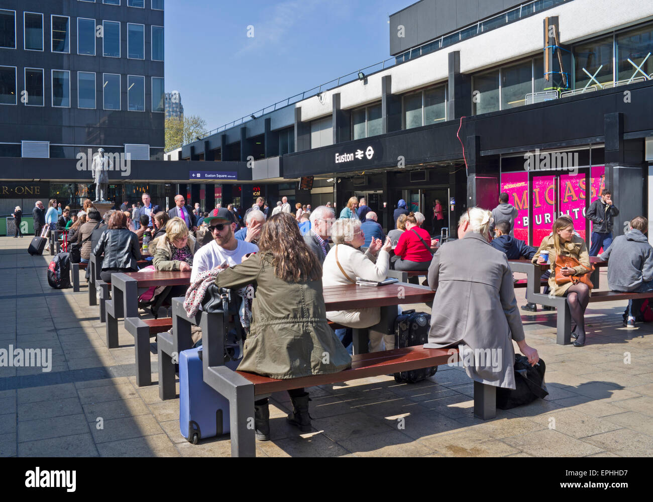 Travellers waiting in sunshine in seating area outside busy Euston Station, (currently undergoing renovation), central - Stock Image