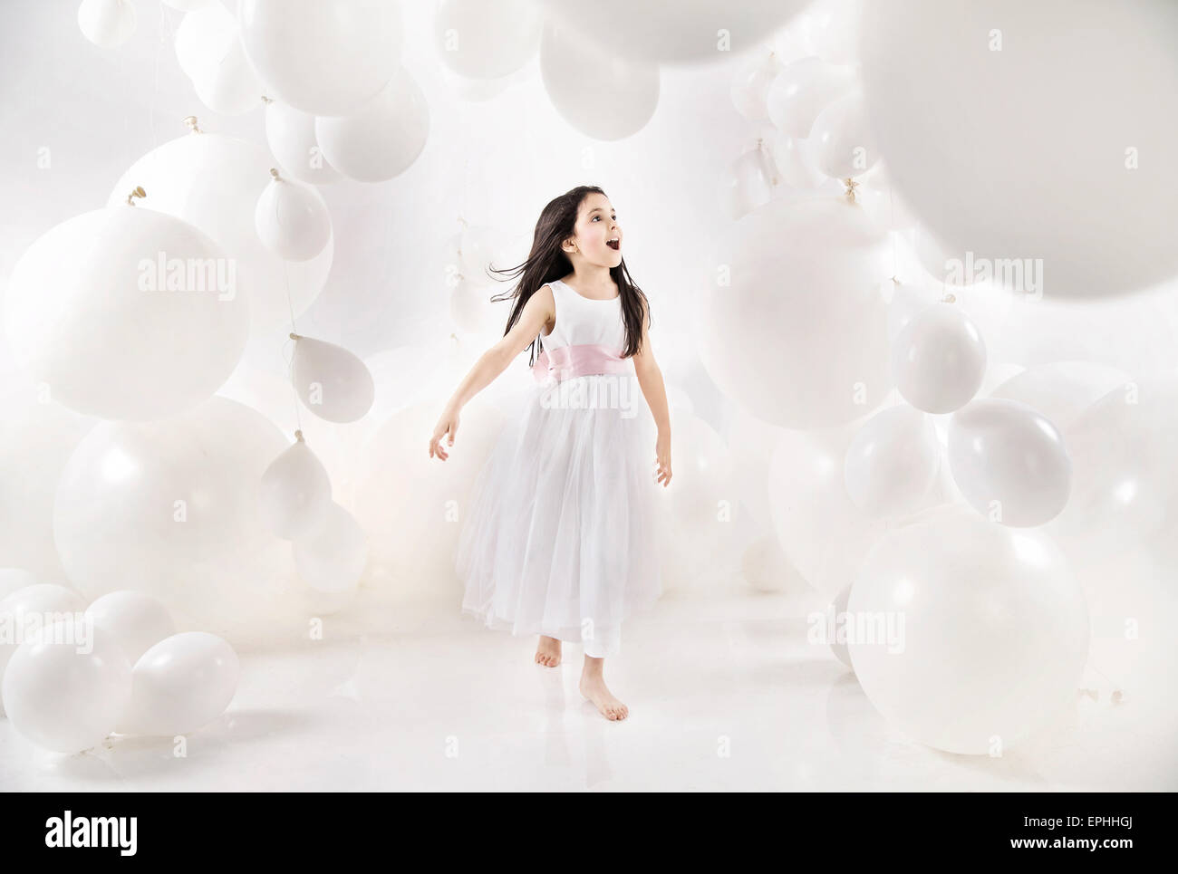 Delighted kid among numerous balloons - Stock Image