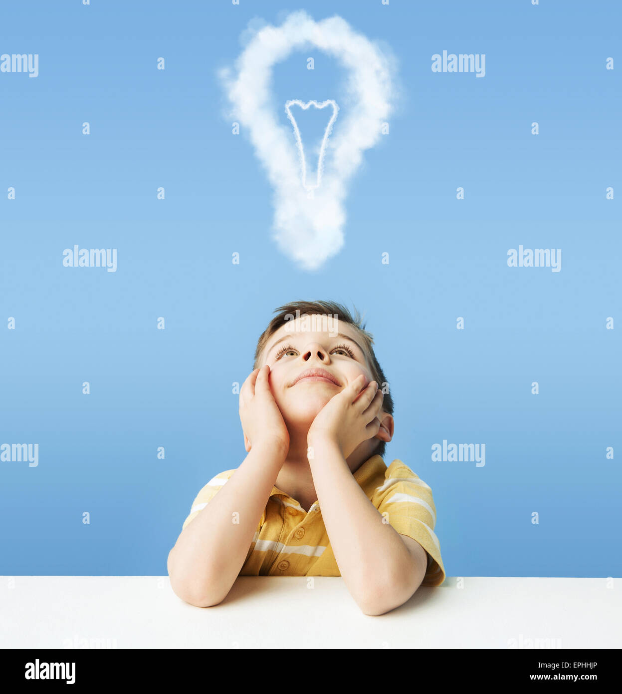 Little kid dreaming about a light bulb - Stock Image
