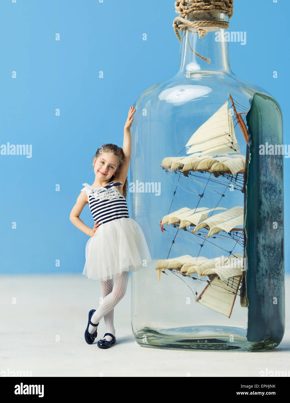 Little lady next to a ship in a bottle - Stock Image
