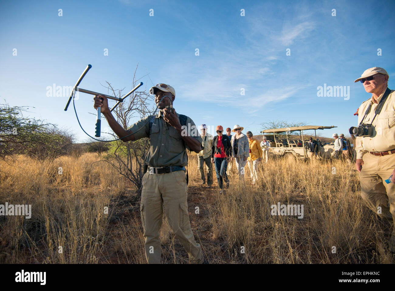 Africa, Namibia. AfriCat Foundation. Tour guide using device. - Stock Image
