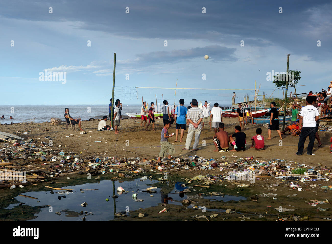 Men playing a game of volleyball on beach covered in plastic trash and other garbage in Sumatra, Indonesia - Stock Image