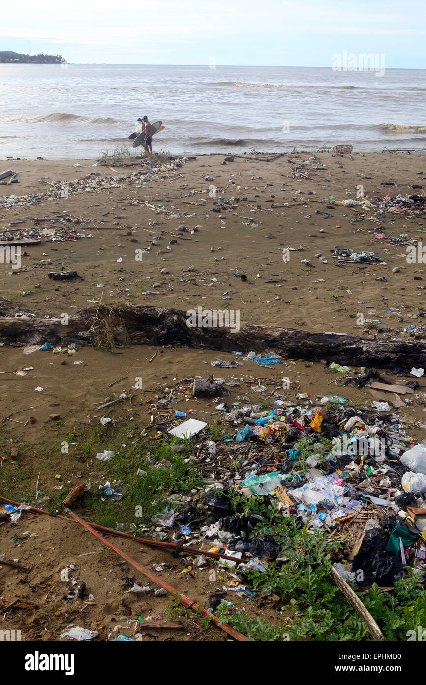 Surfers walk along beach covered in plastic trash and other garbage in Sumatra, Indonesia - Stock Image