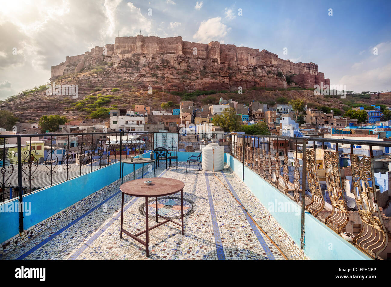 Rooftop cafe with view to Mehrangarh fort on the hill at cloudy sky in Jodhpur Blue city, Rajasthan, India - Stock Image