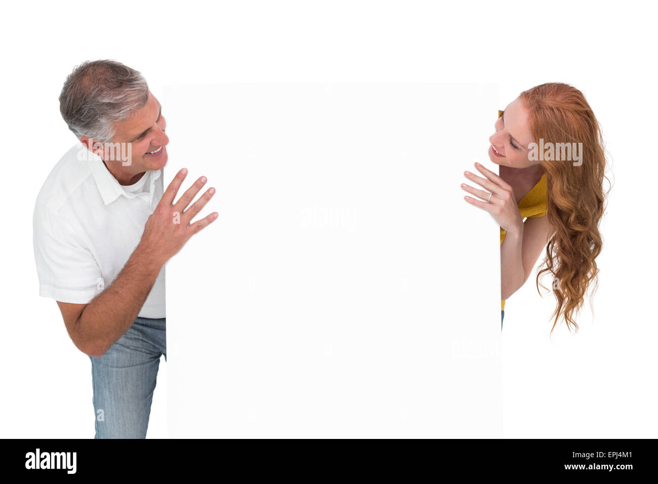 Casual couple showing a poster - Stock Image