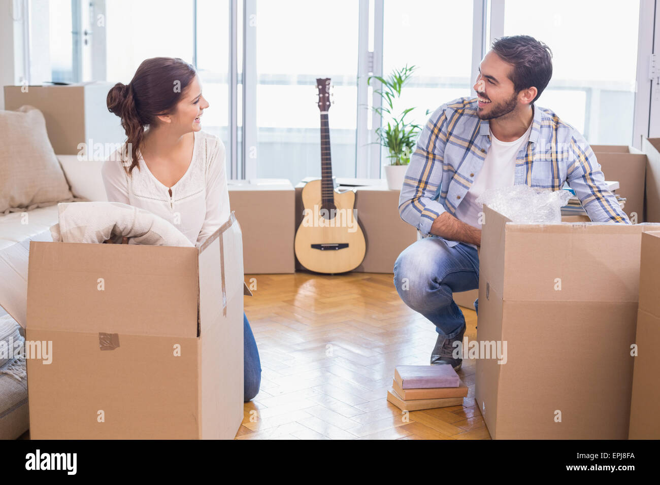 Cute couple unpacking cardboard boxes - Stock Image