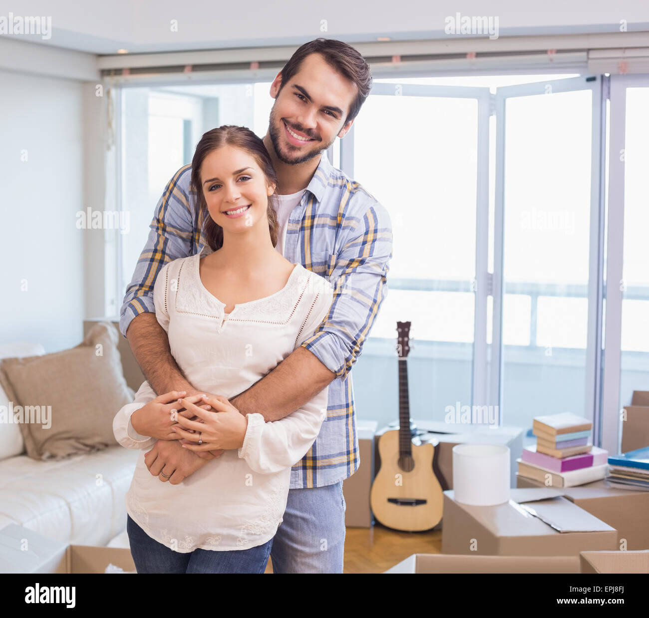 Cute couple hugging and smiling at camera - Stock Image