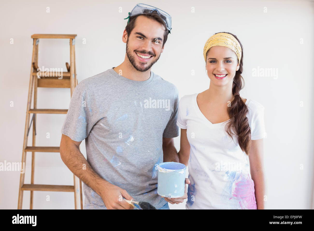 Cute couple redecorating living room - Stock Image