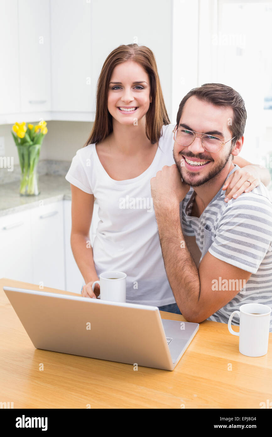 Young couple smiling at the camera using laptop - Stock Image