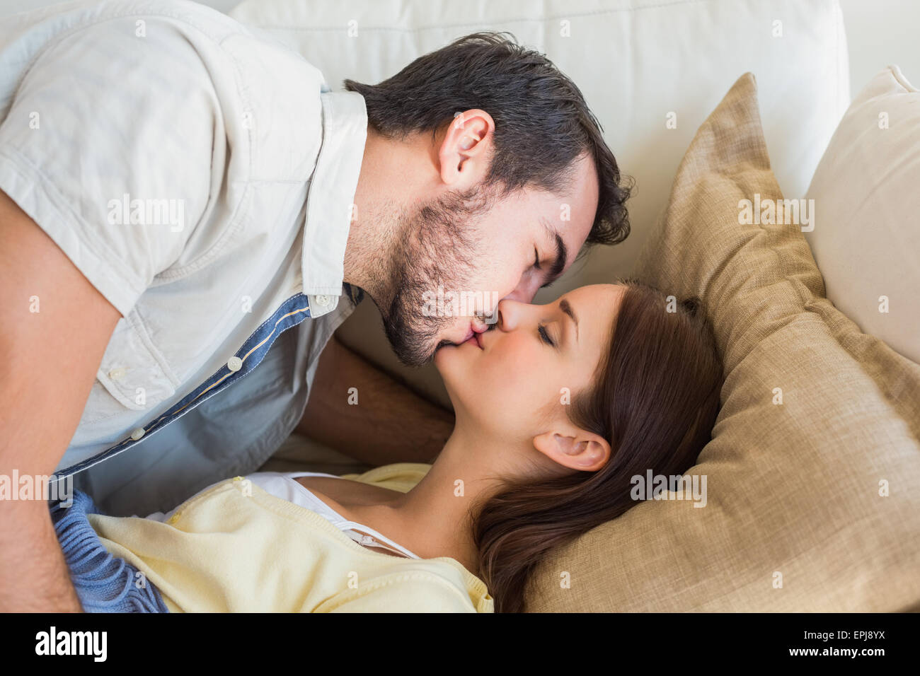 Cute couple kissing on couch - Stock Image