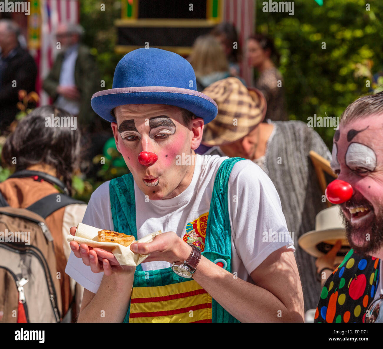 Portrait of a Clown eating a mini pizza - Stock Image