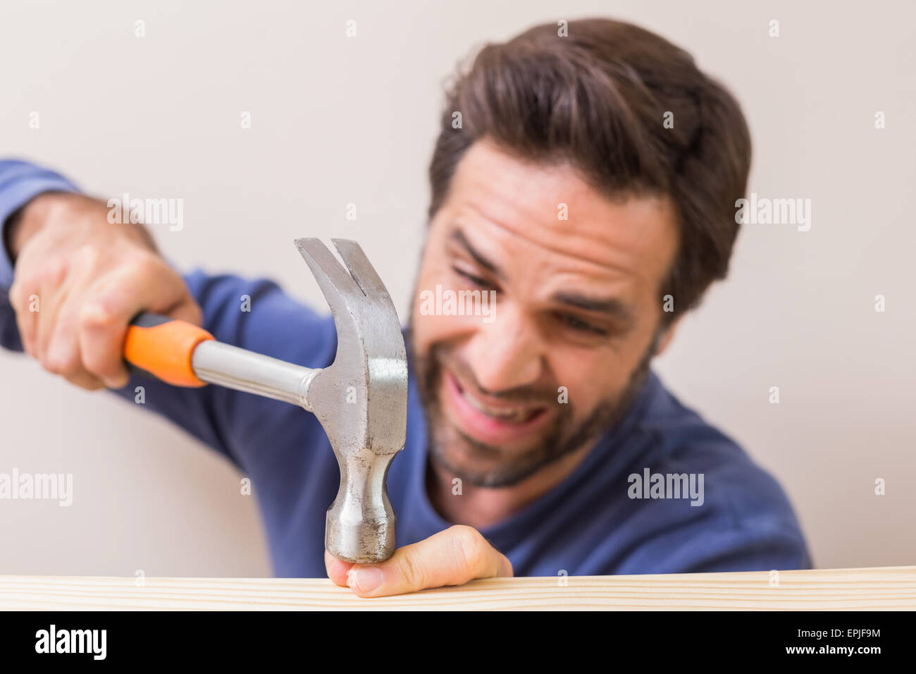 Casual man hammering his finger by accident - Stock Image