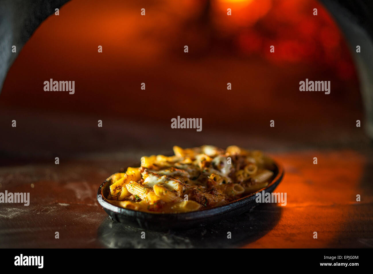 baked penne pasta bolognese with cheese in front of napoli style wood fired oven - Stock Image