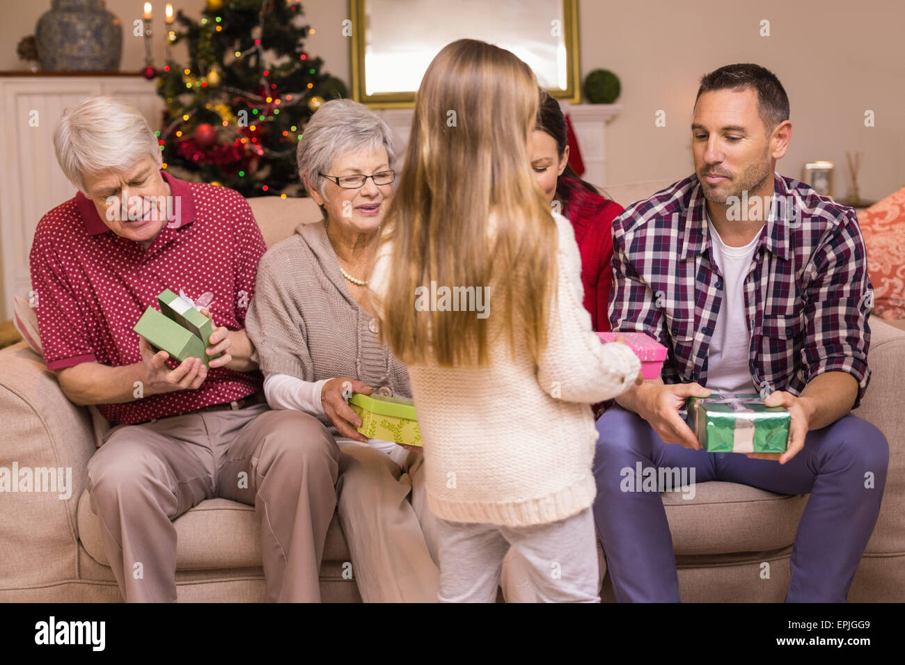 Cute little girl offering gift to her family - Stock Image