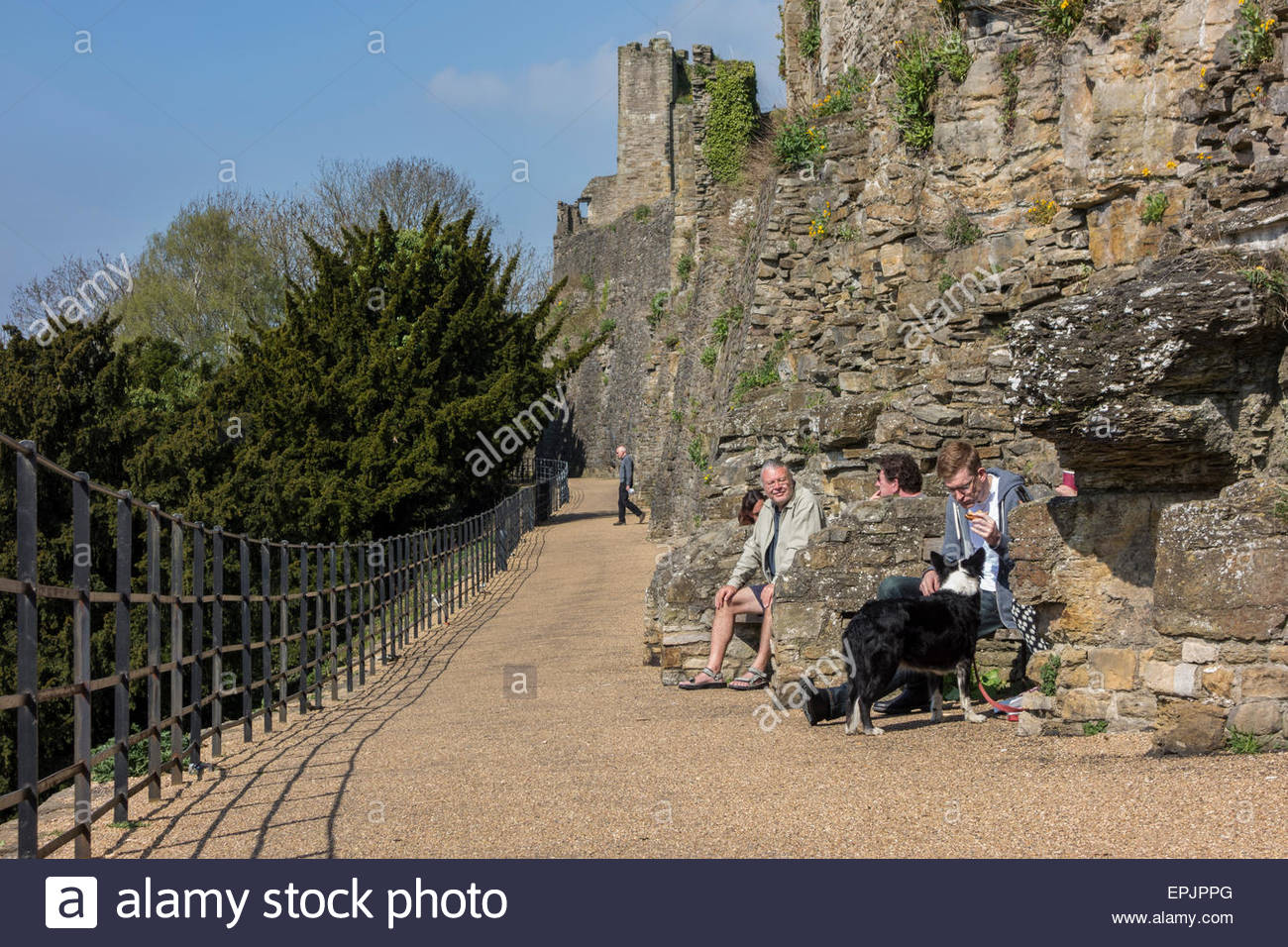 People sitting on benches on Castle walk below Richmond Castle, North Yorkshire Stock Photo