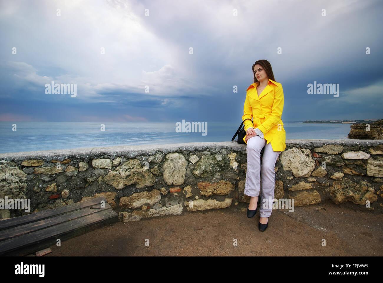 Girl sit on the border. Conceptual scene. - Stock Image