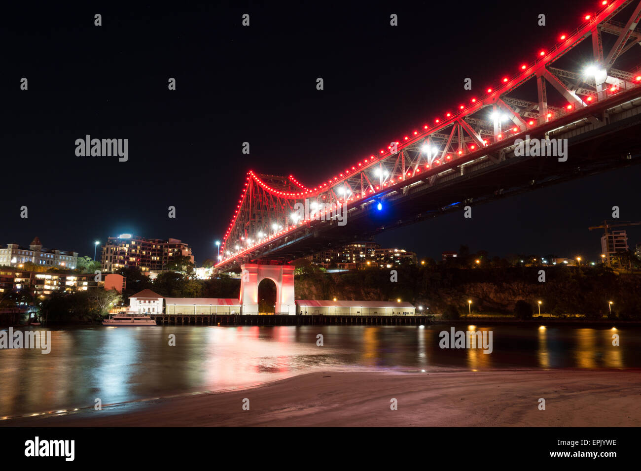 Brisbane Story Bridge in Red with River Bank - Stock Image