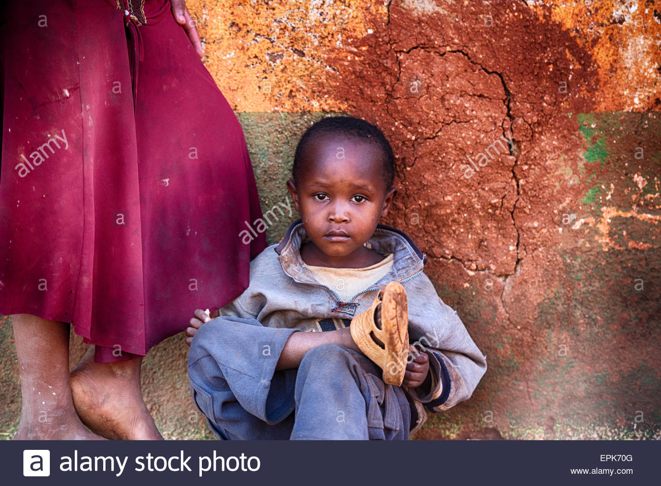 Portrait of an African child, against a textured wall. - Stock Image