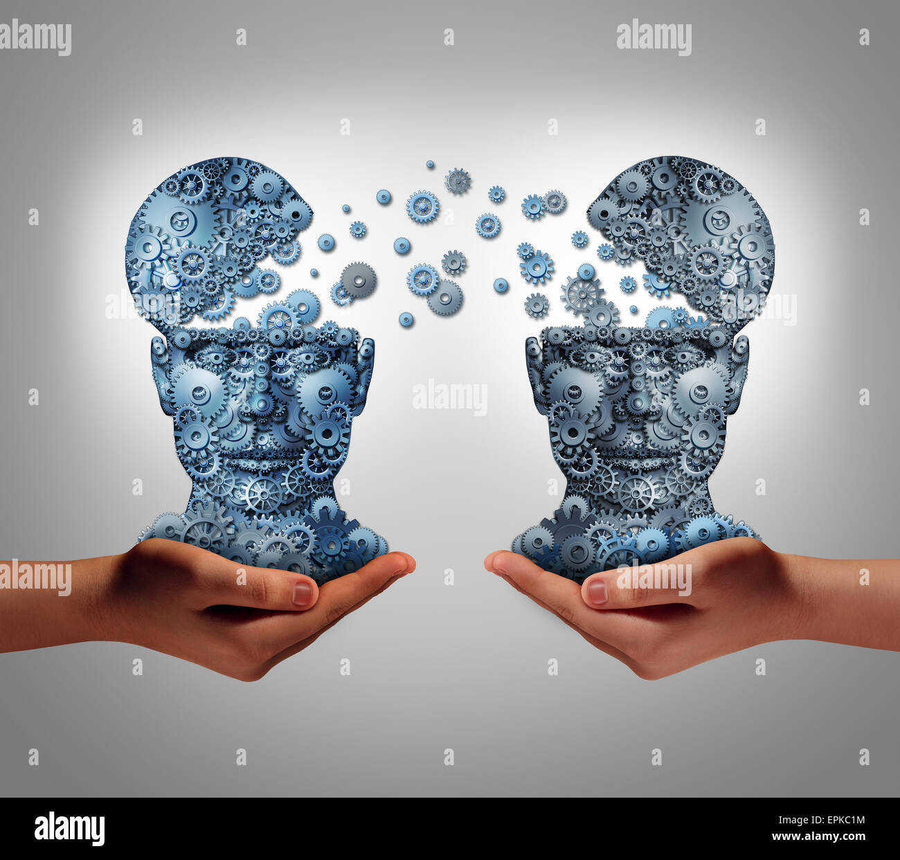 Sharing technology business concept as hands holding two human heads made of gears and cog wheels exchanging information - Stock Image