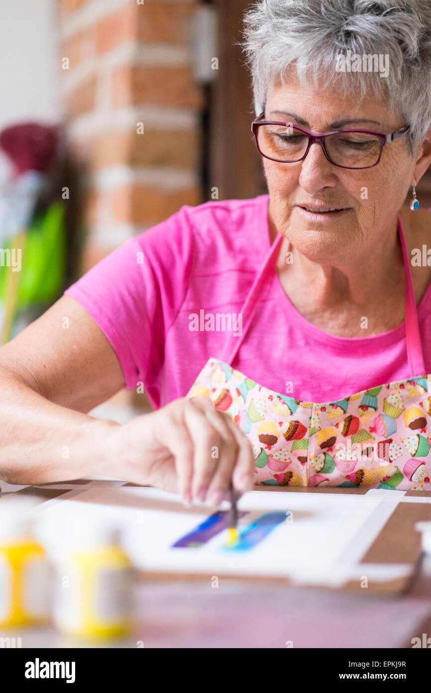 Senior woman painting an abstract picture - Stock Image