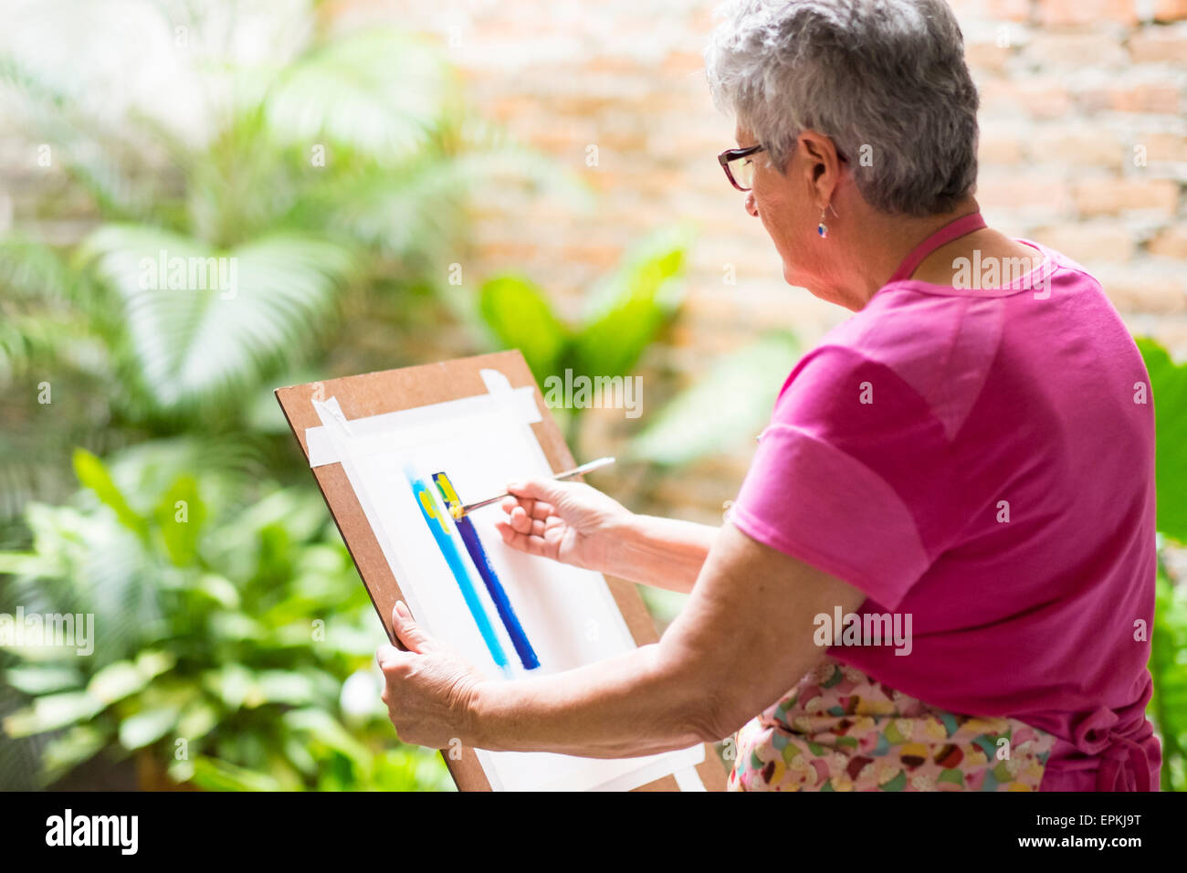 Senior woman painting an abstract picture in her garden - Stock Image