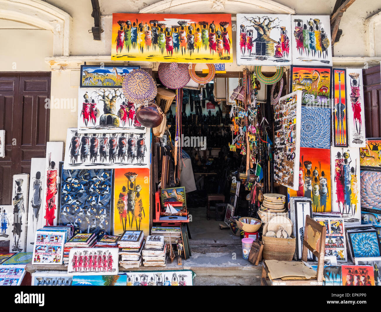 Store selling colorful tinga tinga paintings and other souvenirs to tourists in Stone Town, Zanzibar, Tanzania, - Stock Image