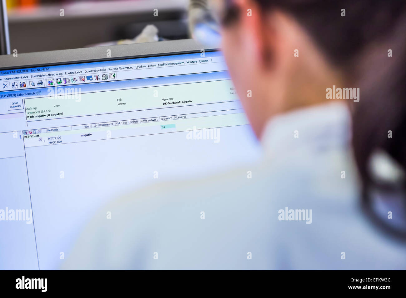 Woman in lab looking at computer monitor - Stock Image