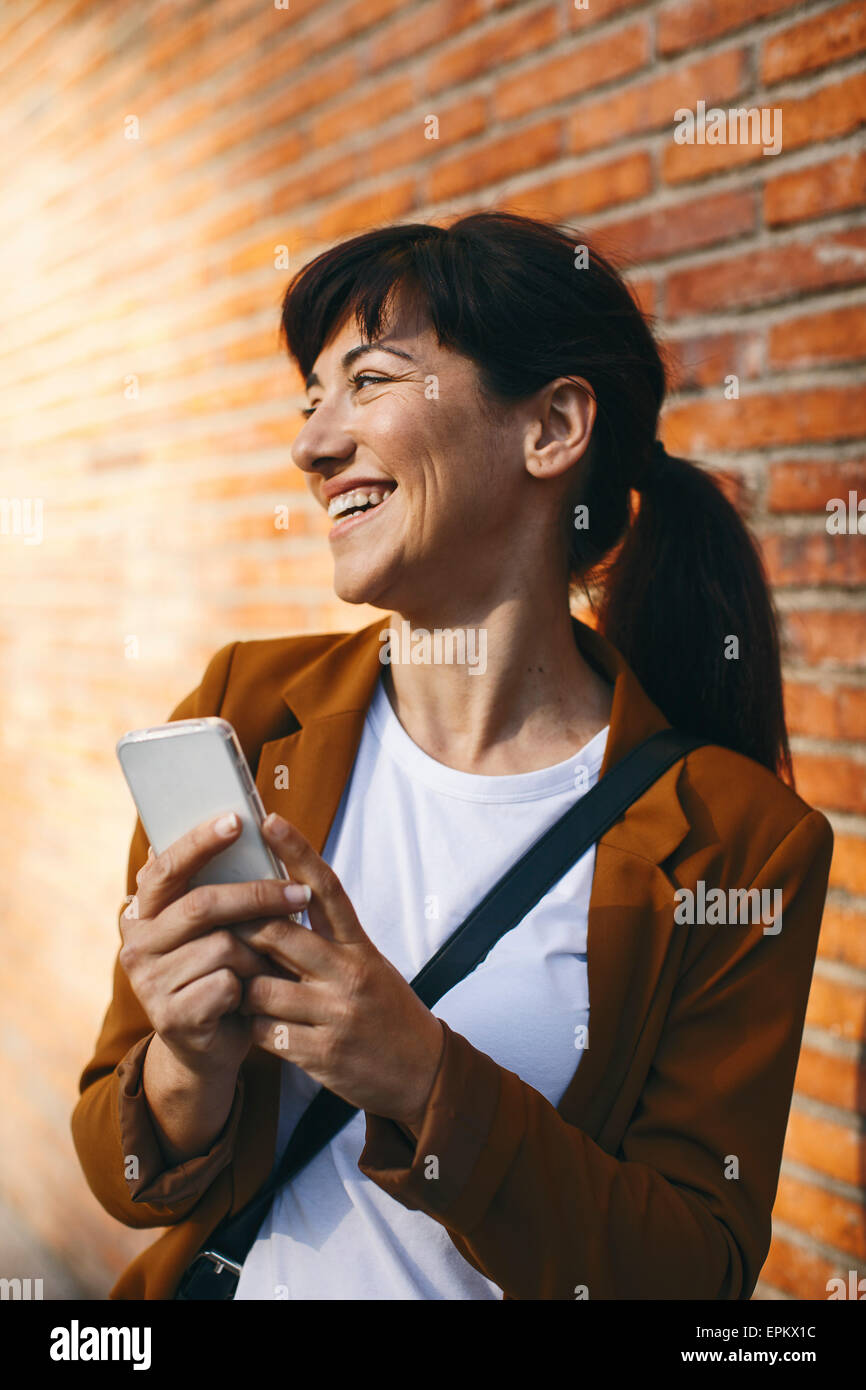 Smiling businesswoman with smartphone - Stock Image