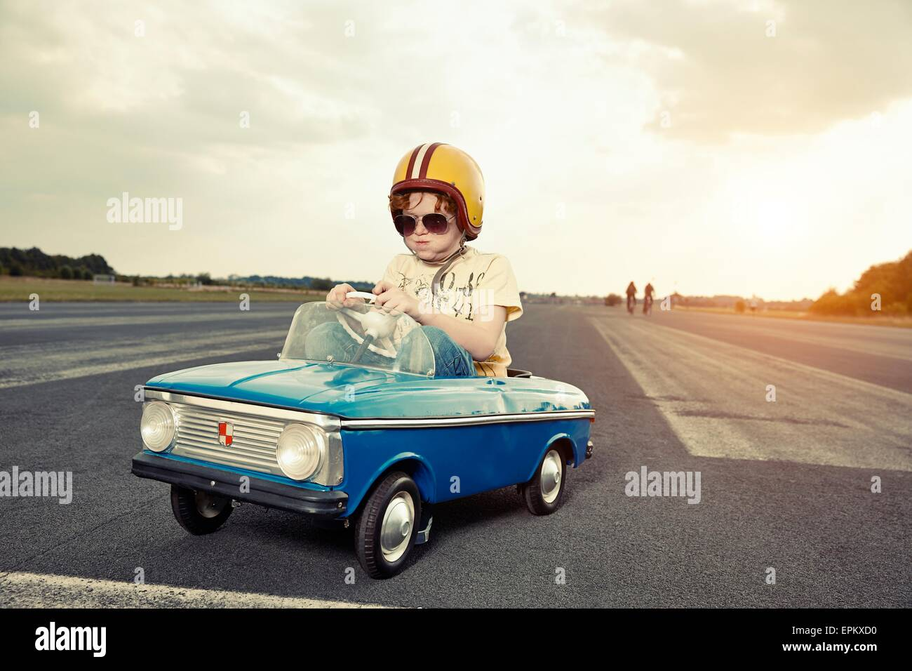 Boy in pedal car on race track - Stock Image