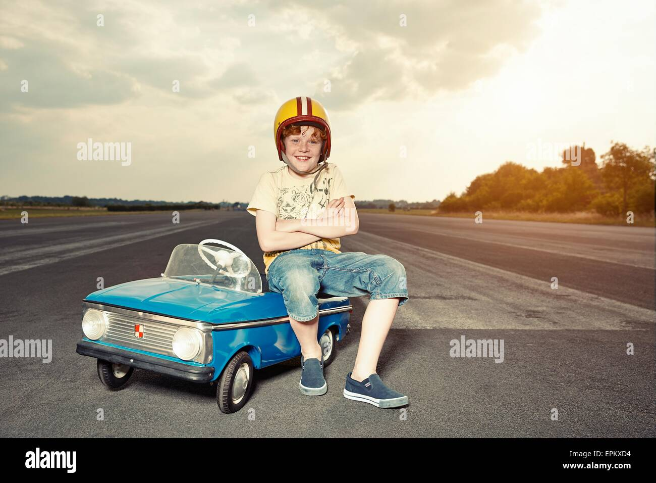 Smiling boy with pedal car on race track - Stock Image