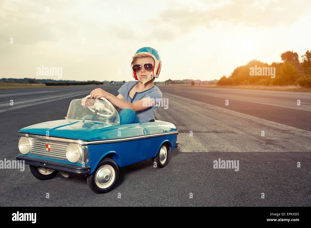 Boy with sunglasses in pedal car on race track - Stock Image