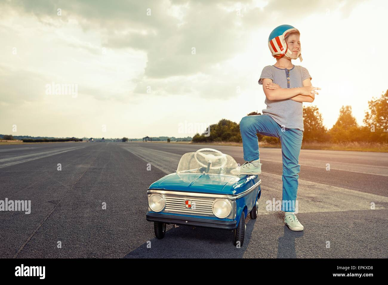 Boy with pedal car on race track - Stock Image