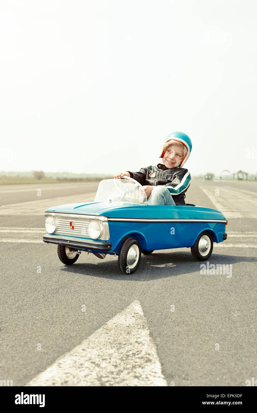 Smiling boy in pedal car on race track - Stock Image