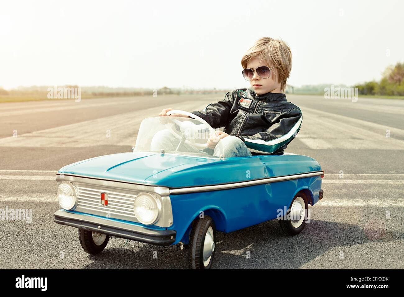 Cool boy in pedal car on race track - Stock Image