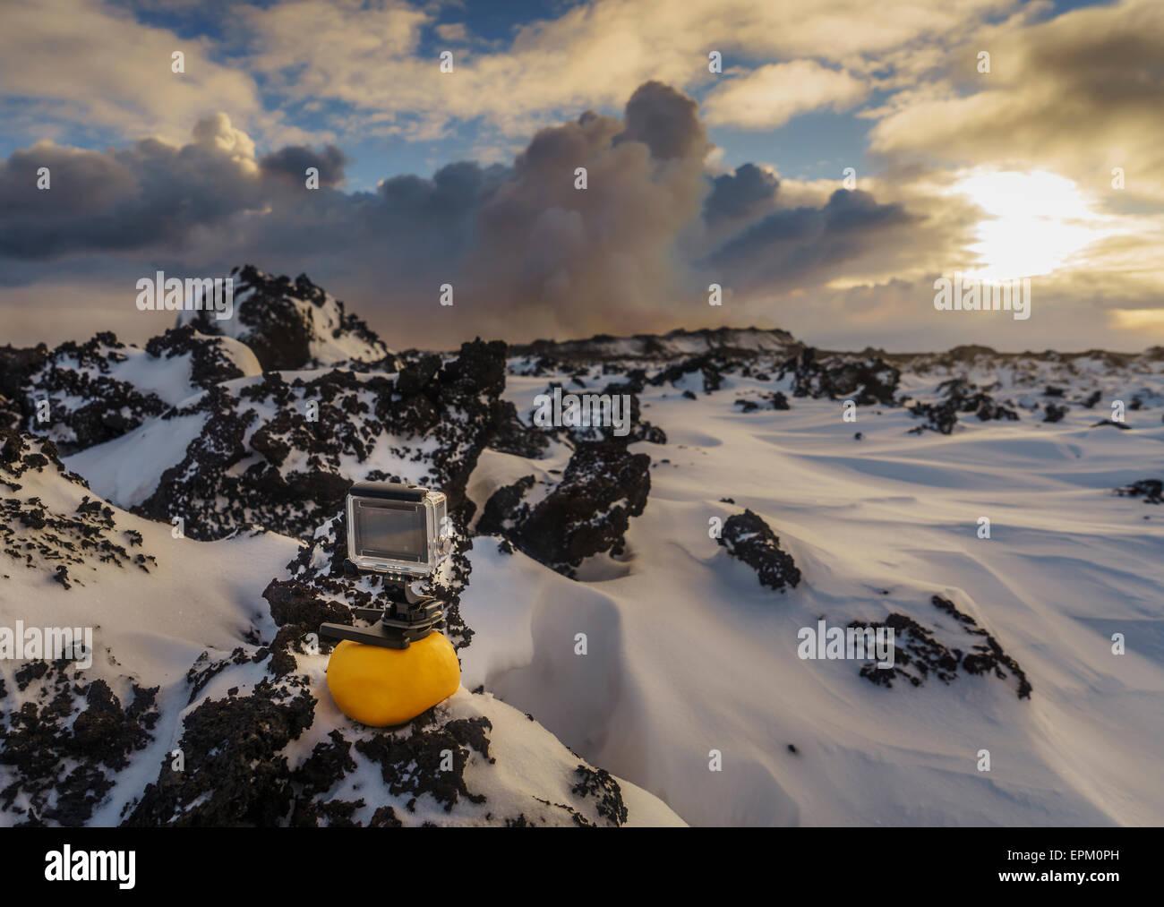 GoPro camera on lava rock, Holuhraun Eruption in the background, Iceland - Stock Image
