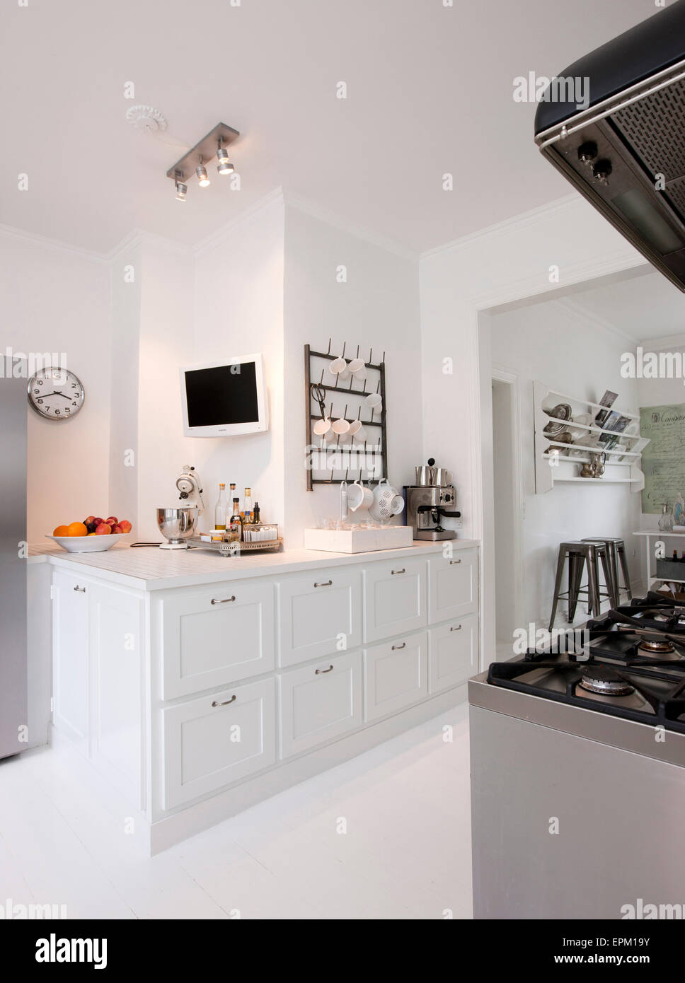 White Kitchen With Range Oven And Wall Mounted Tv In Hanne Davidsen Stock Photo Alamy