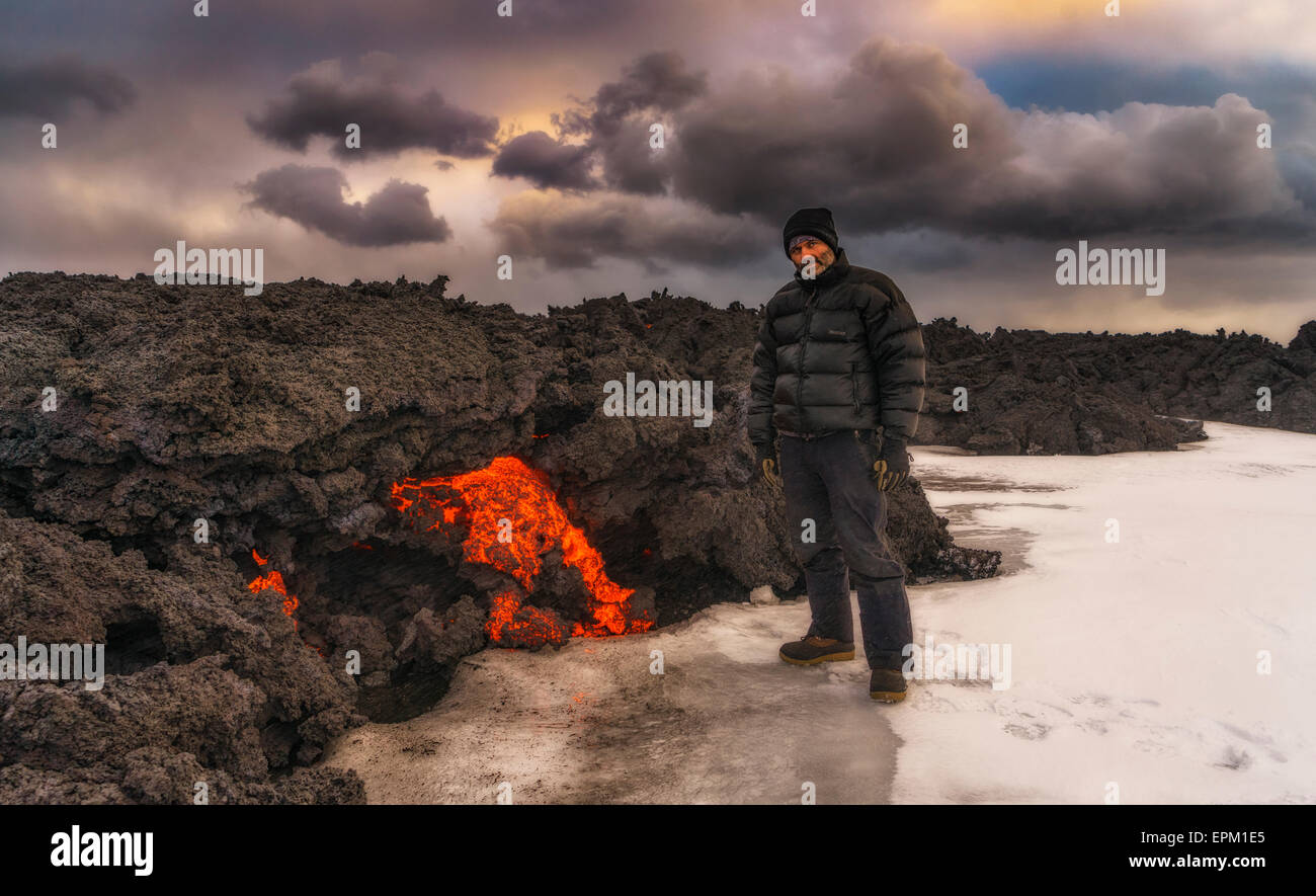 Man standing by glowing lava flow, Holuhraun Fissure Eruption, Bardarbunga Volcano, Iceland - Stock Image