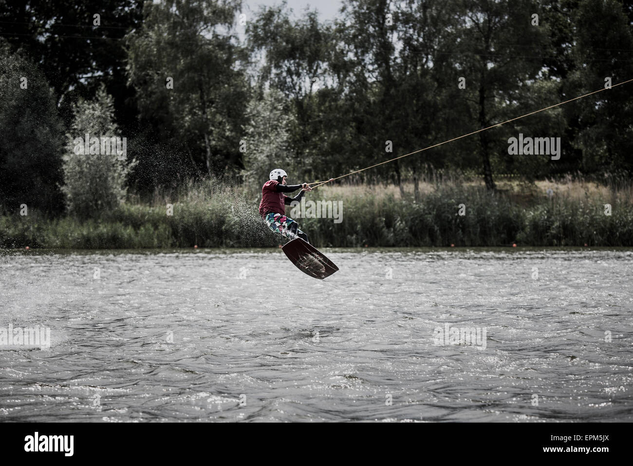 Germany, Garbsen, wakeboarder at Blue Lake jumping in the air - Stock Image