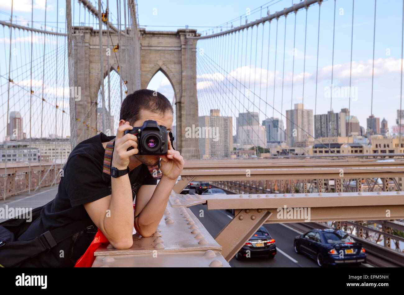 USA, New York, traveller taking pictures of Manhattan from Brooklyn Bridge in the evening - Stock Image