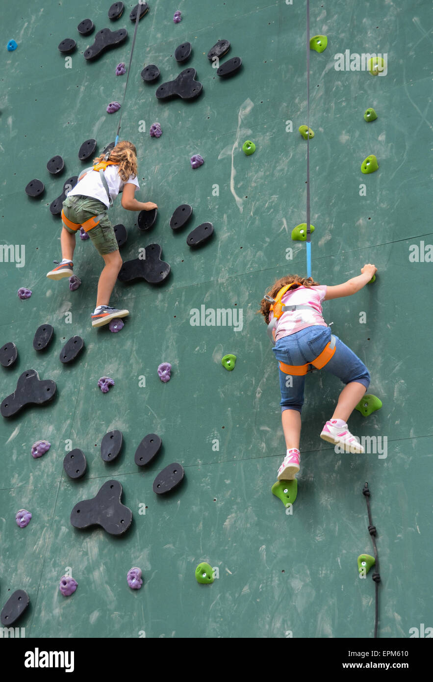 Young girls having an adventure climbing and jumping at a fun park. Here they are climbing up a wall. - Stock Image