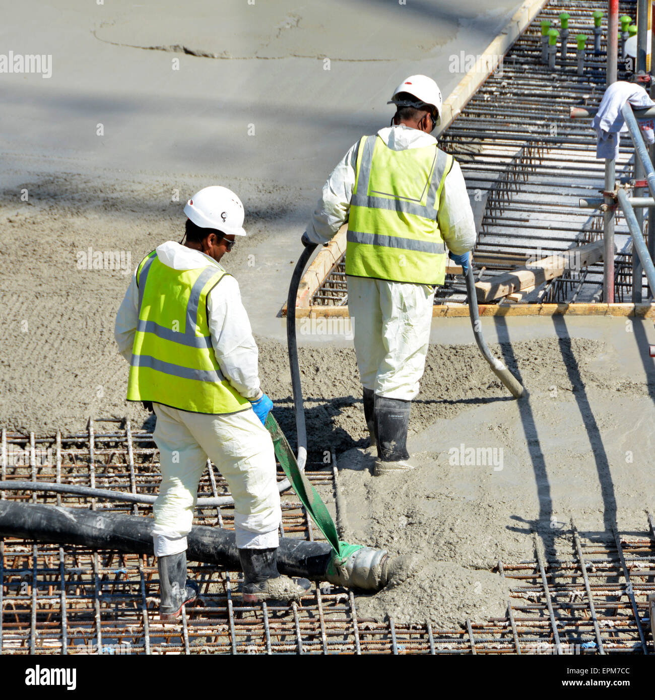 Placing & vibrating pumped concrete into steel reinforcement on new floor slab for apartment block Stock Photo