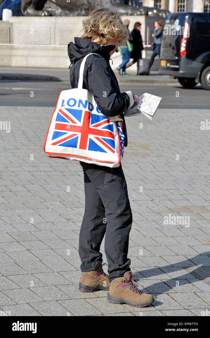 london tourist at trafalgar square with union jack shoulder bag looking at map london england uk