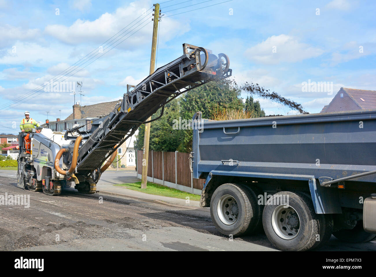 Maintenance road works tipper truck loading with worn out tarmac surface removed by planing machine driver for resurfacing & repairs Essex England UK Stock Photo