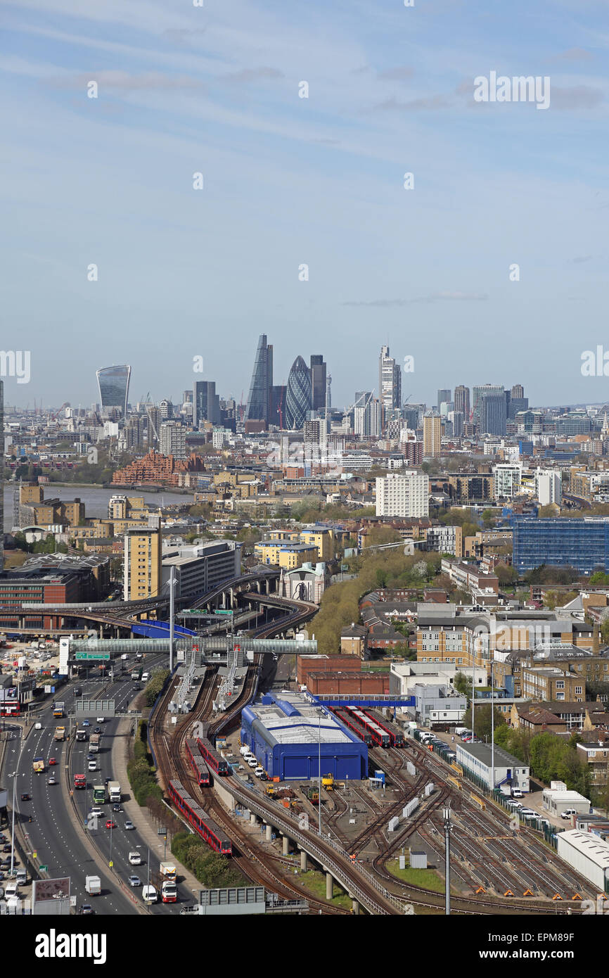High level view of the City of London from the east showing Poplar DLR station and train depot + the Aspen Way dual - Stock Image
