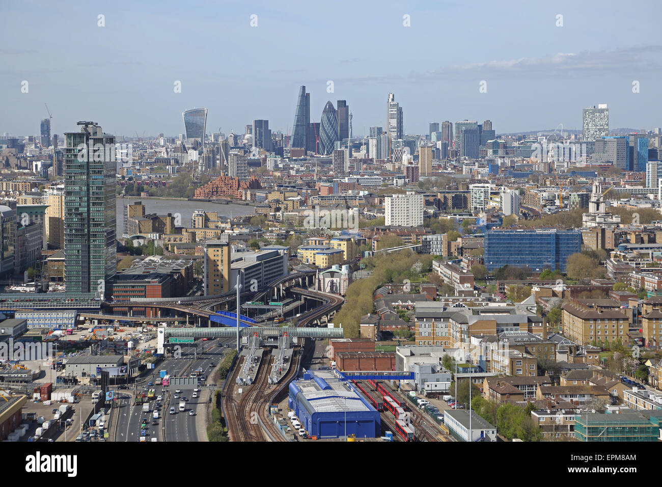 High level view of the City of London from the east showing Poplar DLR station and the Aspen Way dual carriageway - Stock Image