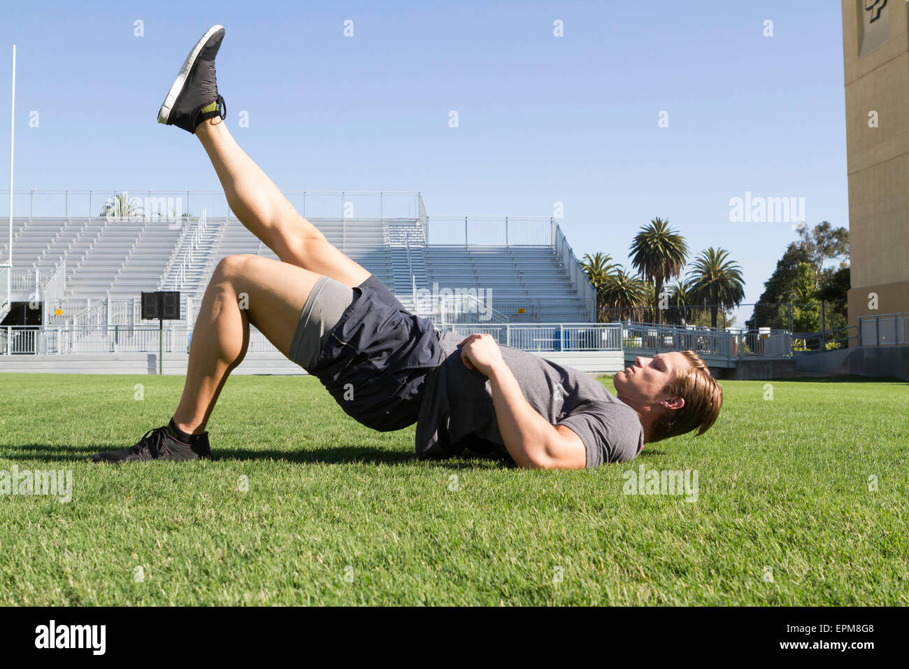 USA, California, San Luis Obispo, young man doing workout on an athletic field - Stock Image