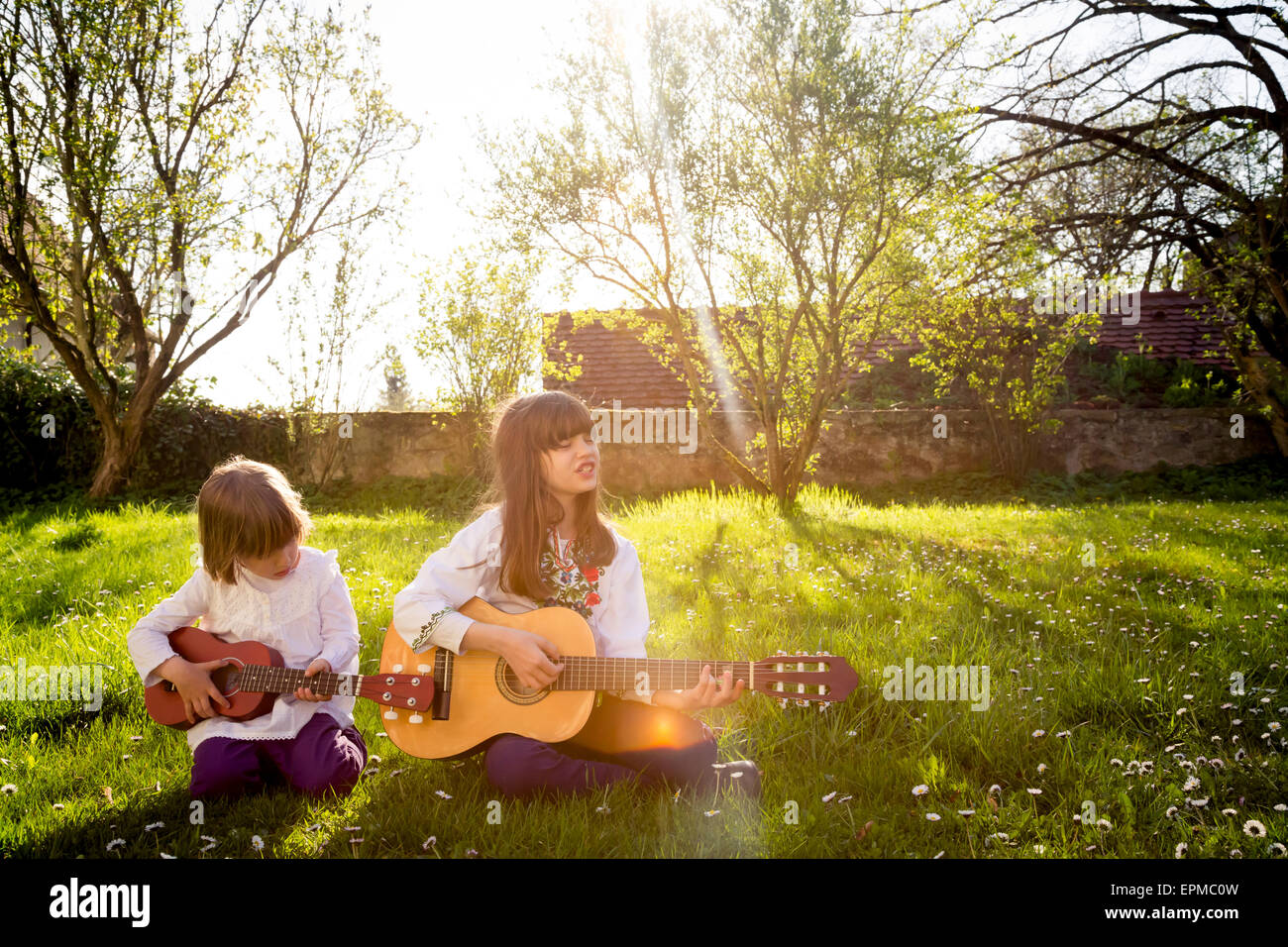 Two sisters sitting on a meadow playing guitar - Stock Image