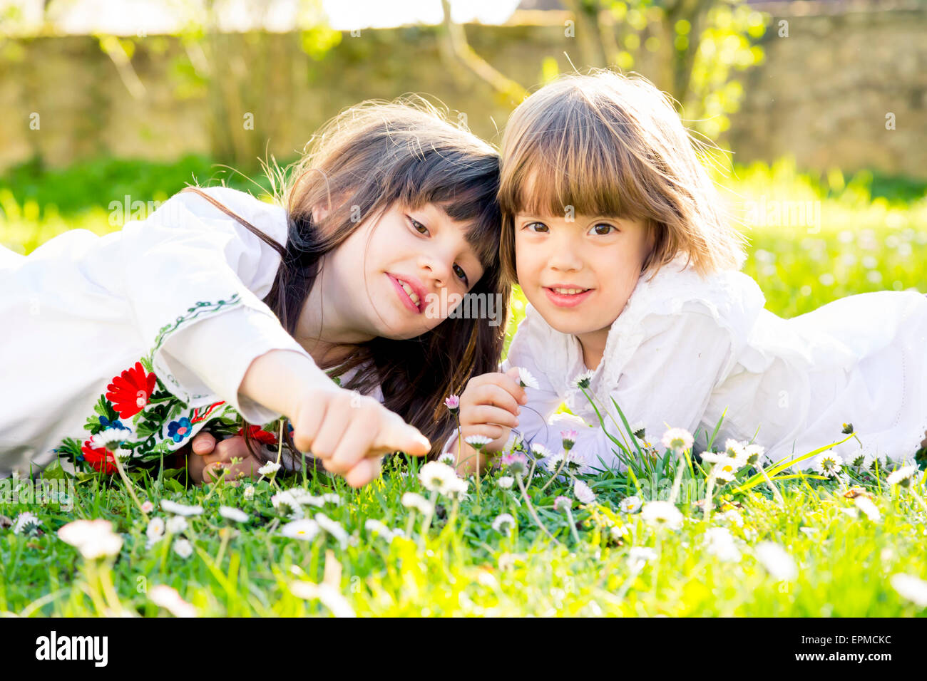 Two sisters lying together on a meadow in the garden - Stock Image