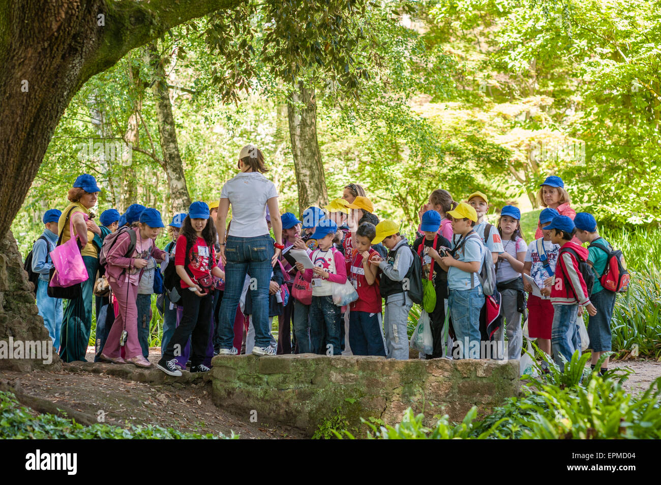 Ninfa, Lazio, Italy. Italian schoolchildren on a visit to the spectacular gardens set in a ruined medieval village - Stock Image